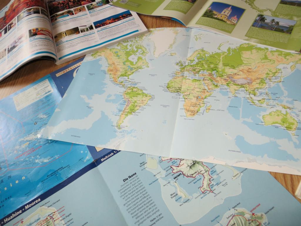 Reiseplanung, mit Landkarte, Magazinen und Reiseführern